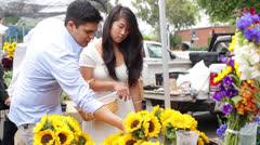 Young Couple Buying Sunflowers at Farmers Market Stock Footage