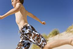 Germany, Baltic sea, Boy (8-9) running down sand dunes Stock Photos