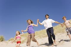 Germany, Baltic sea, Family running down beach dune - stock photo