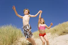 Germany, Baltic sea, Boy (8-9) and girl (6-7) jumping down beach dune Stock Photos