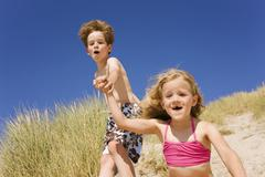 Germany, Baltic sea, Boy (8-9) and girl (6-7) jumping down beach dune - stock photo