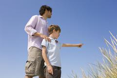 Germany, Baltic sea, Father and son (8-9) on sand dune Stock Photos