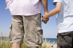 Germany, Baltic sea, Father and son (8-9) holding hands, rear view Stock Photos