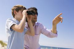 Germany, Baltic sea, Boy (8-9) looking through binoculars, portrait - stock photo