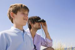 Germany, Baltic sea, Father and son (8-9), father looking through binoculars, - stock photo