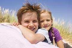 Germany, Baltic sea, Boy (8-9) and girl (6-7) in sand dunes, smiling, portrait, Stock Photos