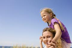 Germany, Baltic sea, Mother carrying daughter (6-7) on shoulders, portrait - stock photo