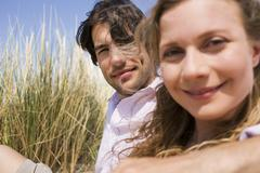 Germany, Baltic sea, Young couple sitting in dunes, portrait - stock photo