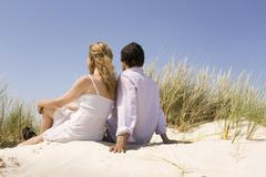 Germany, Baltic sea, Young couple on grassy sand dune, looking out to sea - stock photo