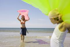 Germany, Baltic sea, Mother and daughter (6-7) carrying airbed Stock Photos
