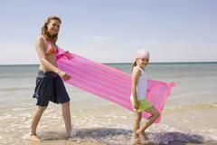 Germany, Baltic sea, Mother and daughter (6-7) carrying airbed, side view - stock photo
