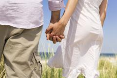 Germany, Baltic sea, Couple holding hands, rear view - stock photo