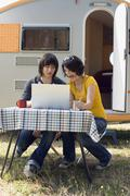 Germany, Leipzig, Ammelshainer See, Young couple sitting by camping trailer Stock Photos