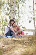 Germany, Leipzig, Ammelshainer See, Couple on blanket by lake - stock photo