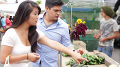 Young Couple Tasting Fruit and Vegetables at Farmers Market Stock Footage