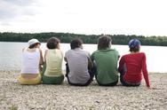 Stock Photo of Germany, Leipzig, Ammelshainer See, Five persons sitting near lake