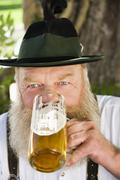Germany, Bavaria, Upper Bavaria, Man drinking beer in beer garden, portrait, Stock Photos