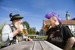 Germany, Bavaria, Upper Bavaria, Man with mohawk hairstyle and Bavarian man in Stock Photos
