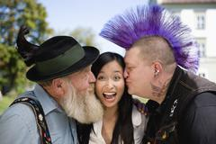 Germany, Bavaria, Upper Bavaria, Two men kissing Asian woman on cheek, portrait - stock photo