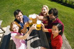 Germany, Bavaria, Upper Bavaria, Cheerful people toasting each other in beer - stock photo