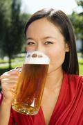 Germany, Bavaria, Upper Bavarian, Asian woman drinking beer, portrait, close-up Stock Photos