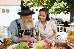 Germany, Bavaria, Upper Bavaria, Asian woman and bavarian man in beer garden Stock Photos