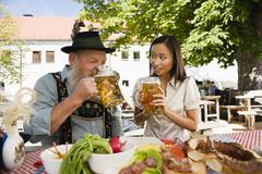 Germany, Bavaria, Upper Bavaria, Bavarian man and Asian woman in beer garden Stock Photos