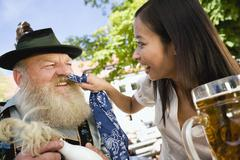 Germany, Bavaria, Upper Bavaria, Bavarian man and Asian woman in beergarden, Stock Photos
