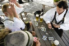 Germany, Bavaria, Upper Bavaria, Men playing cards in beer garden, elevated view - stock photo