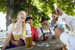 Stock Photo of Germany, Bavaria, Upper Bavaria, People playing cards in beer garden