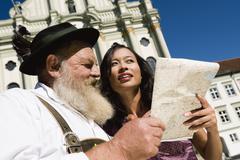 Germany, Bavaria, Upper Bavaria, Asian woman and old Bavarian man looking at - stock photo