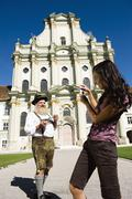 Germany, Bavaria, Upper Bavaria, Asian woman taking picture of Bavarian man with Stock Photos