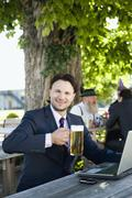 Germany, Bavaria, Upper Bavaria, Young businessman in beergarden holding beer - stock photo