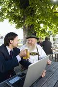 Germany, Bavaria, Upper Bavaria, Senior Bavarian man and young businessman with Stock Photos