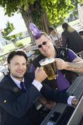 Germany, Bavaria, Upper Bavaria, Businessman and punk in beer garden, elevated - stock photo