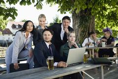 Germany, Bavaria, Upper Bavaria, Young business people in beer garden, portrait - stock photo