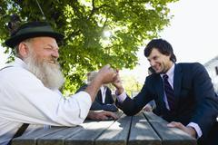 Stock Photo of Germany, Bavaria, Upper Bavaria, Two men in beergarden finger wrestling