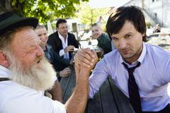 Germany, Bavaria, Upper Bavaria, Two men in beer garden arm wrestling Stock Photos