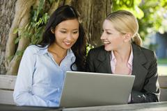 Germany, Bavaria, Upper Bavaria, Two Business women in beer garden using laptop Stock Photos