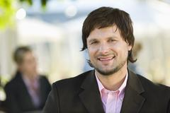 Germany, Bavaria, Upper Bavaria, Young businessman in beer garden, portrait - stock photo