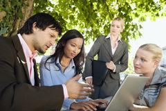 Germany, Bavaria, Upper Bavaria, Business people using laptop in beer garden Stock Photos