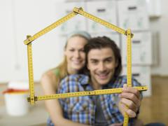 Stock Photo of Young couple making house shape with folding rule, portrait