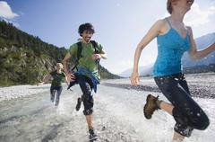 Stock Photo of Germany, Bavaria, Tolzer Land, Young people running through river