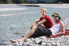 Germany, Bavaria, Tolzer Land, Young couple sitting on riverbank - stock photo