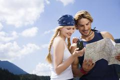 Germany, Bavaria, Tolzer Land, Young couple looking at map and compass - stock photo