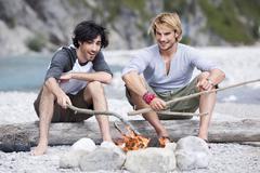 Germany, Bavaria, Tolzer Land, Men sitting at campfire near river - stock photo