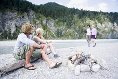 Germany, Bavaria, Tolzer Land, Young people sitting at campfire near river Stock Photos