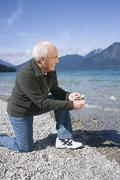 Stock Photo of Germany, Bavaria, Walchensee, Senior man on lakeshore, about to skimming a stone