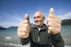 Germany, Bavaria, Walchensee, Senior man rejoicing, thumbs up - stock photo