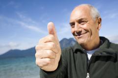 """Germany, Bavaria, Walchensee, senior man giving """"thumbs up"""" Stock Photos"""